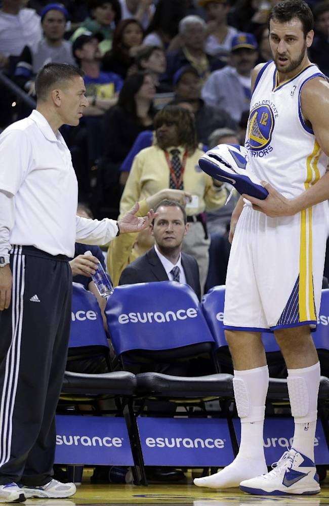 Golden State Warriors' Andrew Bogut, right, holds his shoe that ripped apart during the second half of an NBA basketball game against the Atlanta Hawks Friday, March 7, 2014, in Oakland, Calif