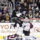 Los Angeles Kings' Anze Kopitar, top, of Slovenia, jumps in front of Colorado Avalanche goalie Semyon Varlamov, right, of Russia, to avoid Colorado Avalanche's Nate Guenin during the first period of an NHL hockey game on Saturday, Nov. 23, 2013, in Los An