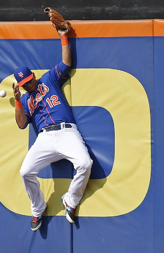 New York Mets center fielder Juan Lagares makes a leaping attempt to catch a double hit by Washington Nationals' Adam LaRoche during the seventh inning of a baseball game Thursday, Sept. 12, 2013, in New York