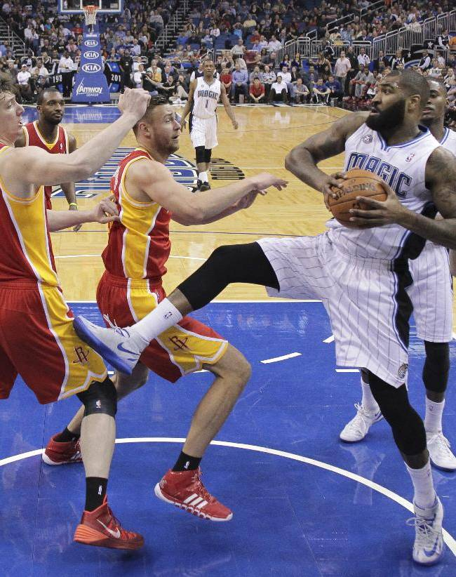 Orlando Magic's Kyle O'Quinn, second from right, grabs an offensive rebound in front of Houston Rockets' Omer Asik (3), Donatas Motiejunas, center, and Jeremy Lin (7) during the first half of an NBA basketball game in Orlando, Fla., Wednesday, March 5, 2014