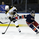 Boston Bruins' David Krejci, left, and New York Rangers' Dan Girardi fight for the puck during the first period of an NHL hockey game on Sunday, March 2, 2014, in New York The Associated Press
