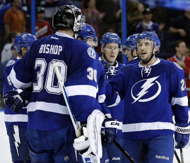 Tampa Bay Lightning right wing Ryan Callahan, right, congratulates goalie Ben Bishop after the team defeated the Montreal Canadiens 3-1 during an NHL hockey game Tuesday, April 1, 2014, in Tampa, Fla