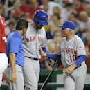 New York Mets' Ike Davis, center, is tended to by a trainer and manager Terry Collins (10) as he leaves the game after being injured batting during the third inning of a baseball game against the Washington Nationals, Saturday, Aug. 31, 2013, in Washingto