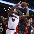 Toronto Raptors' DeMar DeRozan (10) goes to the net against Miami Heat's Mario Chalmers, left, and Michael Beasley, right, during the second half of an NBA basketball game in Toronto, Friday, Nov. 29, 2013 The Associated Press