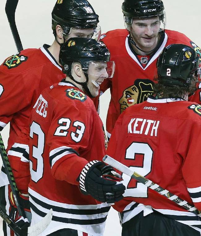 Chicago Blackhawks right wing Kris Versteeg (23) celebrates with teammates after scoring a goal against the San Jose Sharks during the third period of an NHL hockey game on Sunday, Nov. 17, 2013, in Chicago