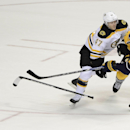 Boston Bruins defenseman Torey Krug (47) loses his stick as he defends Nashville Predators center Colin Wilson (33) in overtime of an NHL hockey game Tuesday, Dec. 16, 2014, in Nashville, Tenn. The Predators won the shootout to win the game 3-2 The Associ