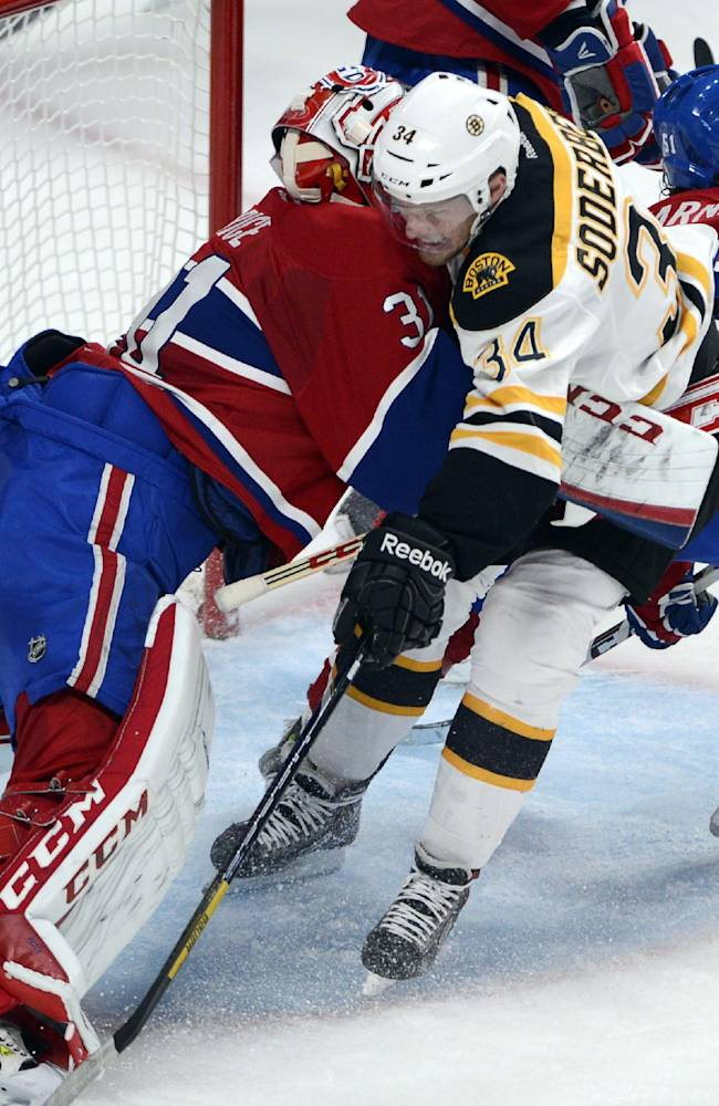 Boston Bruins center Carl Soderberg (34) is sandwiched between Montreal Canadiens goalie Carey Price (31) and center David Desharnais (51) during the second period of Game 3 of an NHL hockey Stanley Cup playoff series, Tuesday, May 6, 2014, in Montreal