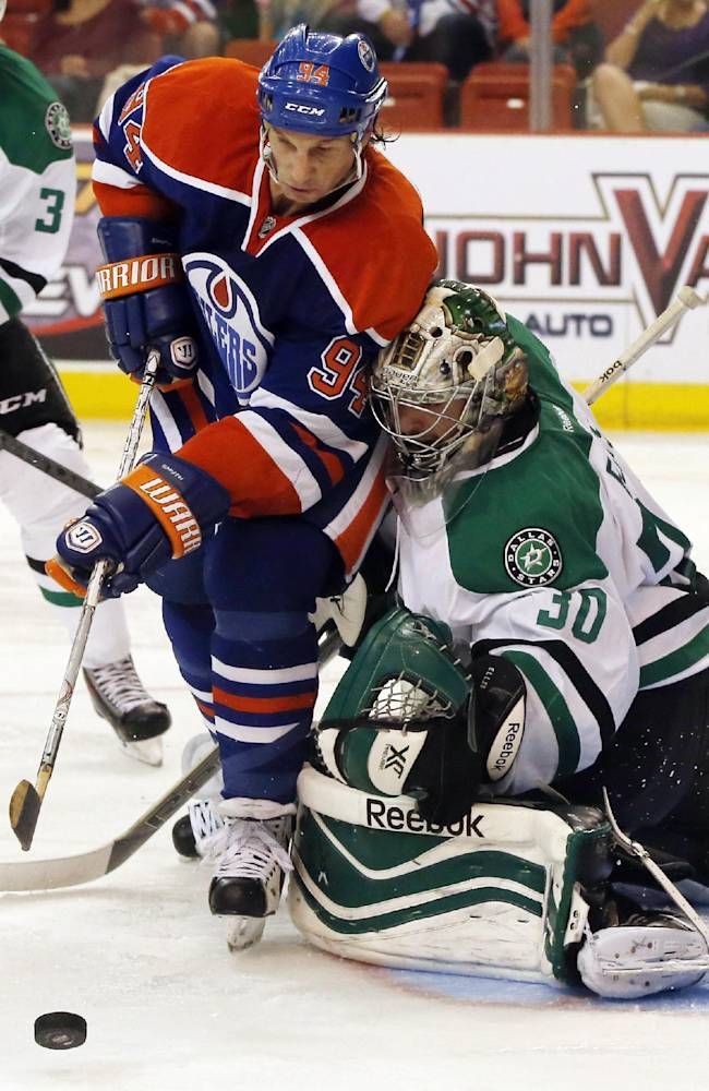 Edmonton Oilers left wing Ryan Smyth (94), of Canada, reaches past Dallas Stars goalie Dan Ellis (30), also of Canada, for the puck in the second period of an NHL preseason hockey game in Oklahoma City, Friday, Sept. 27, 2013
