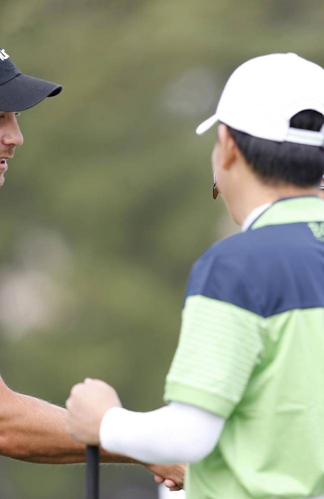 Henrik Stenson of Sweden, left, shake hands with his partners during a pro-am competition ahead of the Masters golf tournament at the Lake Malaren Golf Club in Shanghai, China, Wednesday, Oct. 23, 2013. The Masters will begin on Oct. 24