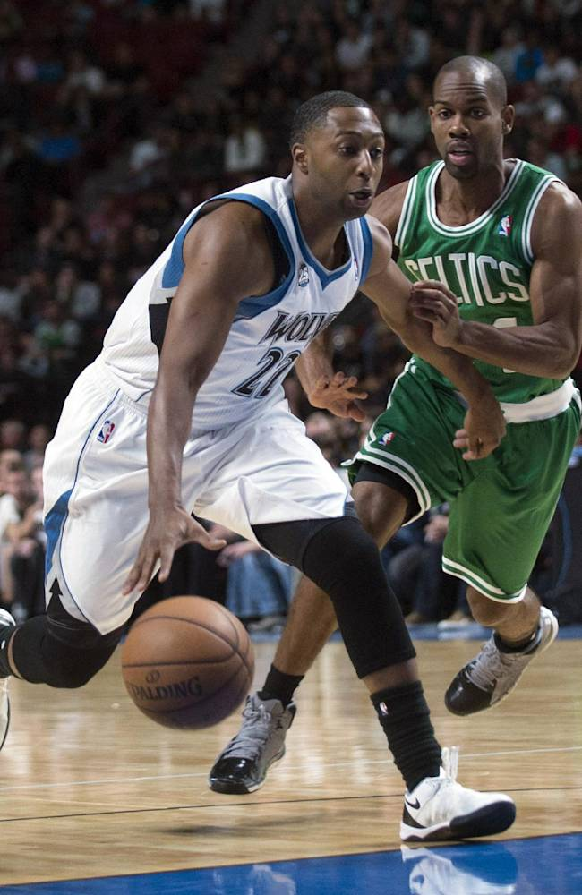 Minnesota Timberwolves' A.J. Price, left, drives to the net as Boston Celtics' Kammron Taylor defends during the fourth quarter of an NBA preseason basketball game in Montreal, Sunday, Oct. 20, 2013