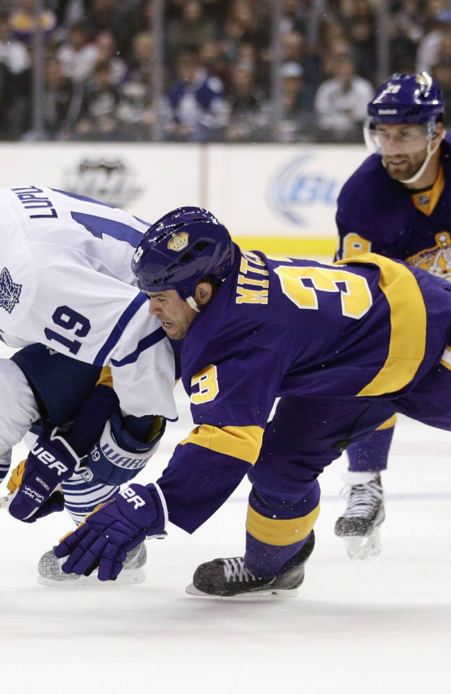 Toronto Maple Leafs' Joffrey Lupul, left, and Los Angeles Kings' Willie Mitchell fight for the puck during the first period of an NHL hockey game on Thursday, March 13, 2014, in Los Angeles