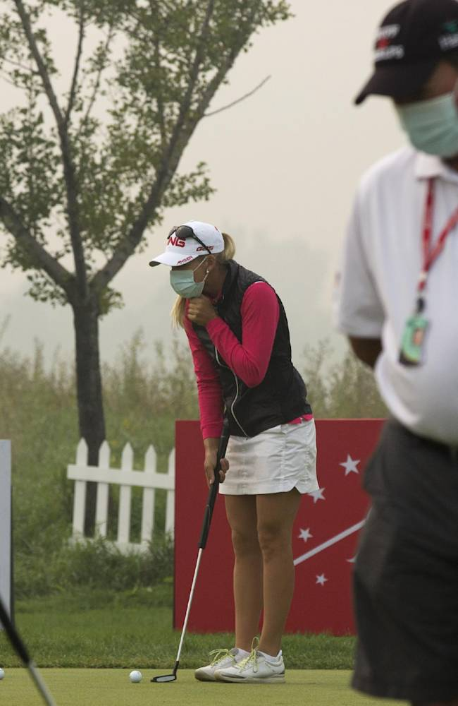 Golfers wear masks as they practice putting on a hazy morning for the third round of the Reignwood LPGA Classic golf tournament at Pine Valley Golf Club on the outskirts of Beijing, China, Saturday, Oct. 5, 2013