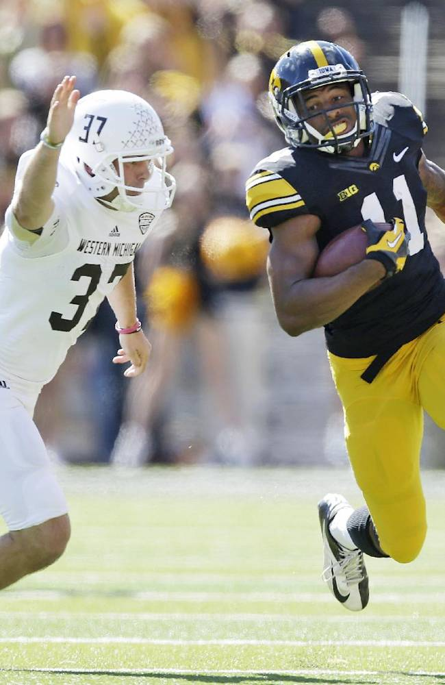 Iowa's Kevonte Martin-Manley (11) runs from Western Michigan punter J. Schroeder, left, during an 83-yard punt return for a touchdown in the first half of an NCAA college football game, Saturday, Sept. 21, 2013, in Iowa City, Iowa