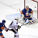 Chicago Blackhawks right wing Patrick Kane (88) shoots the puck past New York Islanders goalie Jaroslav Halak (41) to score as Islanders defenseman Lubomir Visnovsky (11) defends in the third period of an NHL hockey game Saturday, Dec. 13, 2014, in Uniond