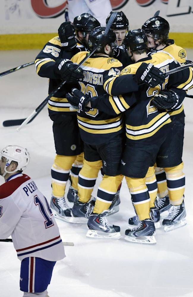Boston Bruins center Carl Soderberg is surrounded by teammates after scoring against Montreal Canadiens goalie Carey Price during the first period of Game 5 in the second-round of the Stanley Cup hockey playoff series in Boston, Saturday, May 10, 2014. Canadiens center Tomas Plekanec (14) skates by