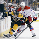Boston Bruins' Patrice Bergeron (37) and Washington Capitals' Troy Brouwer (20) battle for the puck in the second period of an NHL hockey game in Boston, Saturday, March 1, 2014. The Capitals won 4-2 The Associated Press