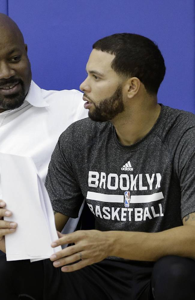 Brooklyn Nets general manager Billy King, left, speaks with Deron Williams during the team's NBA basketball training camp at Duke University in Durham, N.C., Wednesday, Oct. 2, 2013