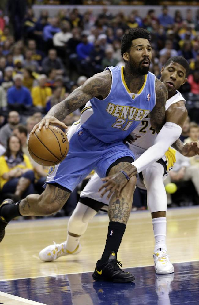 Indiana Pacers forward Paul George, right, reaches around Denver Nuggets forward Wilson Chandler (21) as he drives the baseline in the first half of an NBA basketball game in Indianapolis, Monday, Feb. 10, 2014