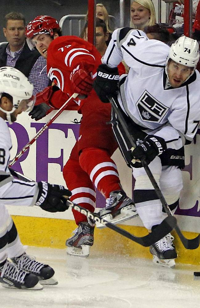Los Angeles Kings' Dwight King, right, competes with Carolina Hurricanes' Brett Bellemore (73) with Kings' Jarret Stoll (28) nearby during the first period of an NHL hockey game, Friday, Oct. 11, 2013, in Raleigh, N.C
