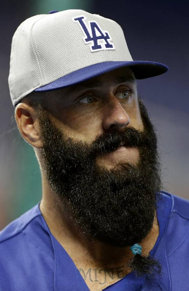 This Aug. 20, 2013 file photo shows Los Angeles Dodgers relief pitcher Brian Wilson watching batting practice before a baseball game against the Miami Marlins,  in Miami. Many a bearded major leaguer disapproves of the bushy black mess hanging low from Brian Wilson's chin these days.  Yet there's no arguing the beard's potential as the relief pitcher chases a third World Series ring in four years