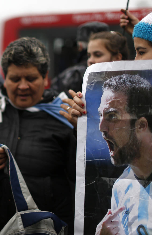 A woman holds an image of Argentina's player Gonzalo Higuain as fans wait for the arrival of Argentina's team to Buenos Aires, Argentina, Monday, July 14, 2014. Fans came out to welcome home Argentina's team after it was defeated 1-0 by Germany at the the Brazil World Cup final match on Sunday