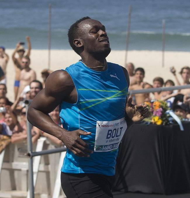Jamaican Olympic gold medallist Usain Bolt, front, smiles after crossing the finish line of the
