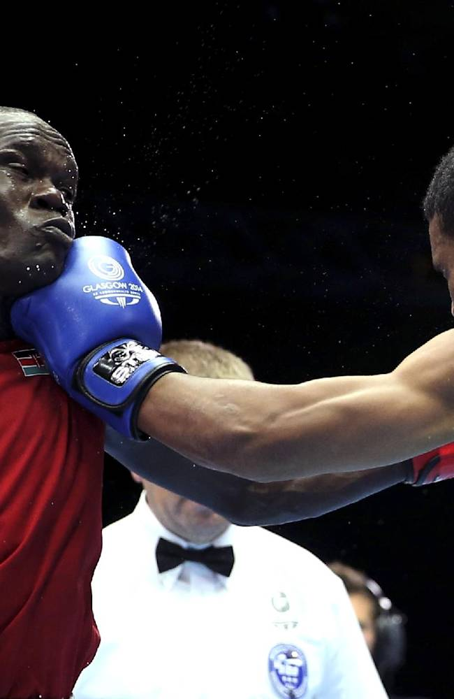 Nauru's Alfonse Deireragea, right, lands a punch on Kenya's Nicholas Okongo Okoth during their men's lightweight preliminary boxing match at the Commonwealth Games Glasgow 2014, in Scotland, Sunday, July 27, 2014
