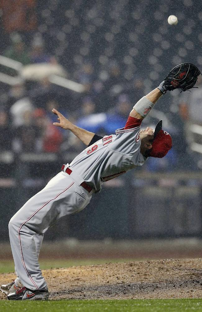Cincinnati Reds first baseman Joey Votto (19) falls backward as he catches a pop fly hit by New York Mets' Juan Lagares for an out in the eighth inning of a baseball game at Citi Field in New York, Friday, April 4, 2014. The Mets won 4-3