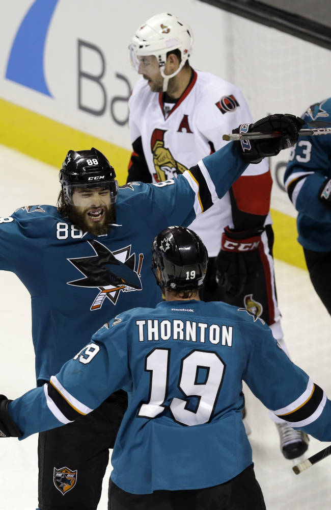 San Jose Sharks' Brent Burns (88) celebrates with teammate Joe Thornton (19) after scoring  the go-ahead goal during the third period of an NHL hockey game against the Ottawa Senators on Saturday, Oct. 12, 2013, in San Jose, Calif. San Jose won 3-2