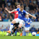 Everton's James McCarthy, front, and Manchester United's Juan Mata battle for the ball during their English Premier League soccer match at Goodison Park in Liverpool, England, Sunday April 20, 2014