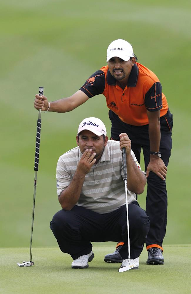Oscar Serna of Mexico, top, lines the putt with his teammate Jose De Jesus Rodriguez at the 6th hole during the third day of the Mission Hills World Cup golf tournament in Haikou, Hainan province, Southern China, Saturday Nov.26, 2011