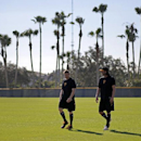 Pittsburgh Pirates pitchers Mark Melancon, left, and Jason Grilli, right, walk in the outfield after running sprints during an informal workout at Pirates City in Bradenton, Fla., Wednesday, Feb. 12. The first official day of baseball spring training fo