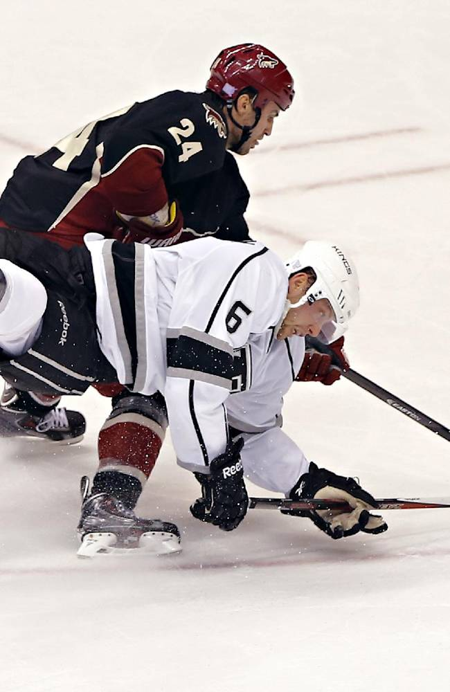 Los Angeles Kings' Jake Muzzin (6) and Phoenix Coyotes' Kyle Chipchura battle for the puck during the third period of an NHL hockey game on Tuesday, Oct. 29, 2013, in Glendale, Ariz. The Coyotes won 3-1