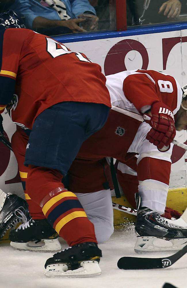 Florida Panthers' Mike Weaver (43) and Detroit Red Wings' Justin Abdelkader (8) battle for the puck during the second period of an NHL hockey game in Sunrise, Fla., Thursday, Feb. 6, 2014