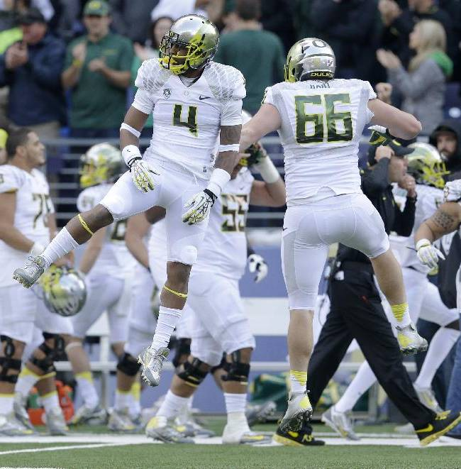 Oregon's Erick Dargan (4) and Taylor Hart (66) celebrate after Dargan intercepted a pass against Washington in the first half of an NCAA college football game, Saturday, Oct. 12, 2013, in Seattle