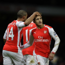 Arsenal's Theo Walcott, left, celebrates scoring his side's second goal with Alexis Sanchez during the English Premier League soccer match between Arsenal and Leicester City at the Emirates Stadium in London, Tuesday, Feb. 10, 2015. (AP Photo/Matt Dunham)