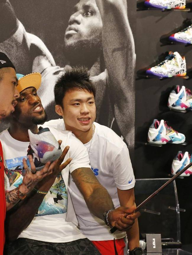 NBA star LeBron James uses his fan's smartphone to take a selfie during a promotional event at a shopping district in Hong Kong as part of his China tour Wednesday, July 23, 2014. Earlier this month, James left the Miami Heat after four seasons and four trips to the NBA Finals and re-signed with the Cavaliers, where his career began
