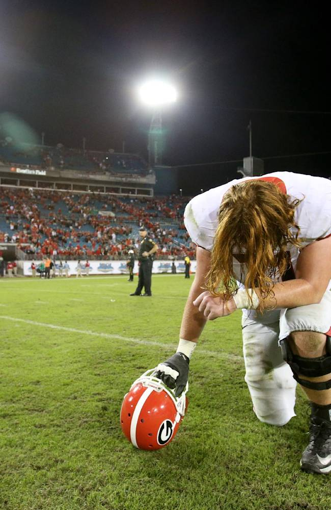 Georgia offensive tackle John Theus, a Jacksonville native, prays on the field following Georgia's 23-20 win over Florida after an NCAA football game, Saturday, Nov. 2, 2013 at Alltel Stadium in Jacksonville, Fla