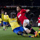 Manchester United s Shinji Kagawa, right, fights for the ball against Arsenal s Bacary Sagna during their English Premier League soccer match at Old Trafford Stadium, Manchester, England, Saturday Nov. 10, 2013