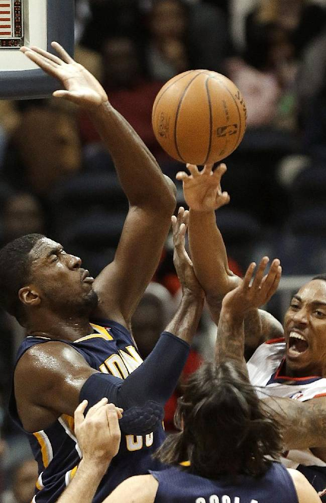 Atlanta Hawks point guard Jeff Teague, right, passes as Indiana Pacers center Roy Hibbert (55) defends during the first half of an NBA basketball game Wednesday, Jan. 8, 2014, in Atlanta, THe Hawks won 97-87