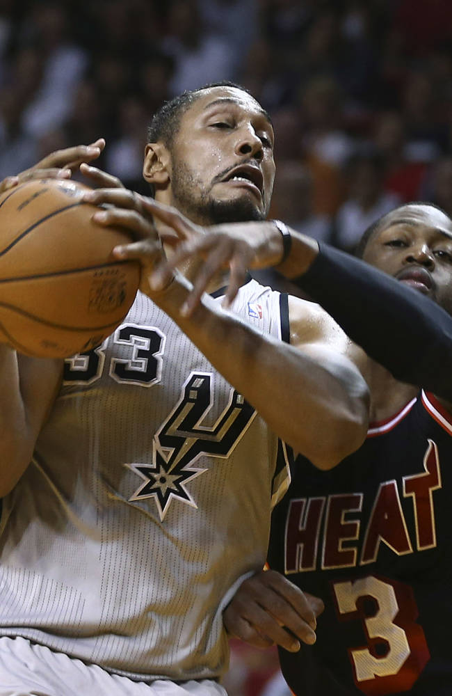 Miami Heat's Dwyane Wade (3) knocks the ball from San Antonio Spurs' Borks Diaw (33) hands during the first half of a NBA basketball game in Miami, Sunday, Jan. 26, 2014