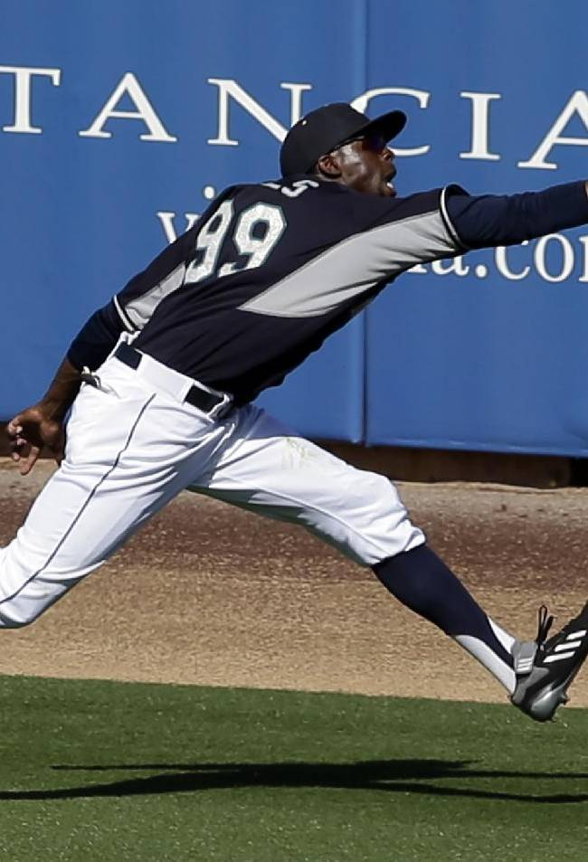 Seattle Mariners' James Jones is unable to reach a run-scoring triple by Cleveland Indians' Elliot Johnson off a pitch from Mariners reliever Lucas Luetge in the seventh inning of a spring training baseball game, Wednesday, March 5, 2014, in Peoria, Ariz