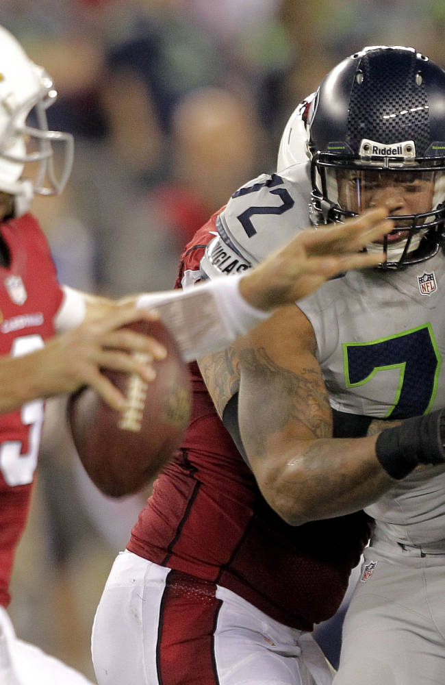 Arizona Cardinals quarterback Carson Palmer (3) is pressured by Seattle Seahawks defensive end Michael Bennett (72) during the first half of an NFL football game, Thursday, Oct. 17, 2013, in Glendale, Ariz