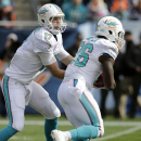 Miami Dolphins quarterback Ryan Tannehill (17) hands off to running back Lamar Miller (26) during the first half of an NFL football game against the Chicago Bears Sunday, Oct. 19, 2014 in Chicago The Associated Press