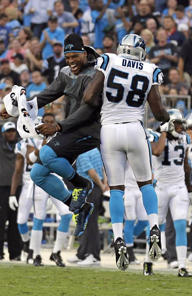 Carolina Panthers' Cam Newton, left, celebrates with Thomas Davis, right, after the defense stopped the Buffalo Bills on fourth down during the first half of a preseason NFL football game in Charlotte, N.C., Friday, Aug. 8, 2014