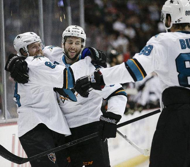 San Jose Sharks' Jason Demers, center, celebrates his goal with Joe Pavelski, left, and Brent Burns during the first period of an NHL hockey game against the Anaheim Ducks on Wednesday, April 9, 2014, in Anaheim, Calif