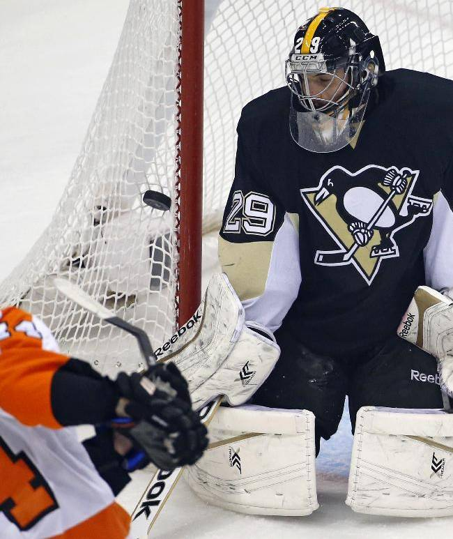 Pittsburgh Penguins goalie Marc-Andre Fleury (29) blocks a shot by Philadelphia Flyers' Sean Couturier (14) in the first period of an NHL hockey game in Pittsburgh, Saturday, April 12, 2014