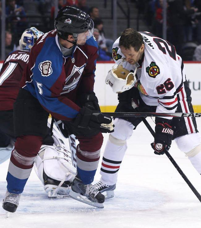 Colorado Avalanche defenseman Nate Guenin, left, pulls off the helmet of Chicago Blackhawks center Michal Handzus, of Slovakia, as they battle for position in front of the net in the second period of an NHL hockey game in Denver on Wednesday, March 12, 2014