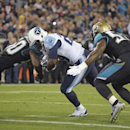 Tennessee Titans running back Leon Washington, center, scores a touchdown on an 8-yard pass play as he gets between Jacksonville Jaguars outside linebacker Telvin Smith, left, and middle linebacker J.T. Thomas during the first half of an NFL football game