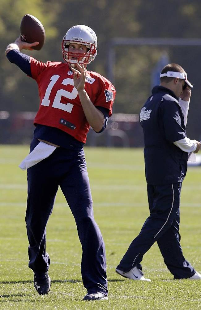 New England Patriots quarterback Tom Brady (12) throws a pass during a stretching and drills session before practice begins at the NFL football team's facility in Foxborough, Mass., Wednesday, Oct. 2, 2013. Patriots offensive coordinator Josh McDaniels walks by at right